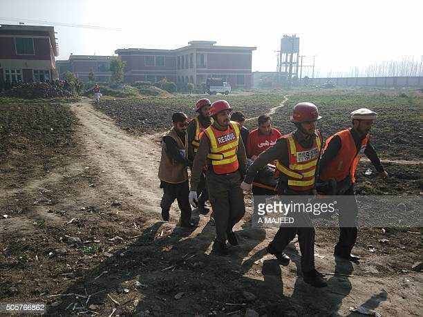 TOPSHOT Pakistani rescuers shift an injured victim outside the Bacha Khan university following an attack by gunmen in Charsadda about 50 kilometres...