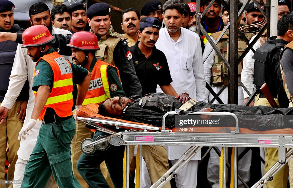 Pakistani rescuers transport an injured police commando on a stretcher at one of two mosques stormed by gunmen in Lahore on May 28, 2010. Gunmen stormed two minority sect mosques, taking worshippers hostage and sparking gun battles with police that have left 17 people dead, officials said. Gunfire and blasts rang out as the attackers, at least one of whom wore a suicide vest, stormed a mosque in the upscale neighbourhood Model Town and another in the busy Garhi Shahu area as people gathered for Friday prayers.