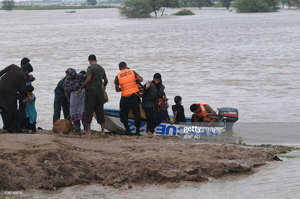 Pakistani rescuers transport flood-affected residents through flood waters at Kala Shah Kako on August 18, 2013. Heavy monsoon rains have triggered floods affecting more than 300,000 people across Pakistan in the last two weeks and killed 108 others, disaster management officials said. AFP PHOTO/Arif ALI