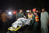 Pakistani rescuers use a stretcher to shift a body from a bomb blast site in Lahore on March 27 2016 At least 25 people were killed and dozens...