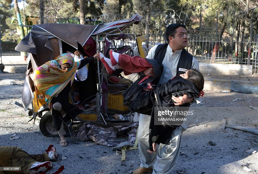 A Pakistani resident carries an injured women as others climb out of a damaged auto rickshaw at the site of a bomb explosion that targeted a security convoy in Quetta on February 6, 2016. A bomb blast struck a paramilitary vehicle and killed at least eight people and wounded more than 35 others in southwestern Pakistani city of Quetta, official said. AFP PHOTO / BANARAS KHAN / AFP / BANARAS KHAN