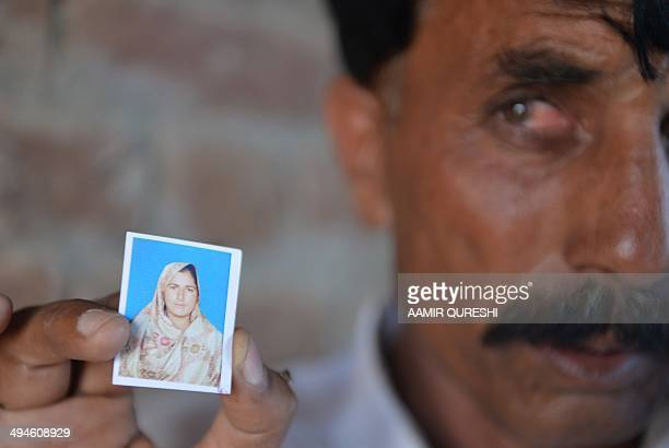 Pakistani resident Mohammad Iqbal poses for a photograph as he holds up an image of his wife Farzana Parveen who was beaten to death with bricks by...