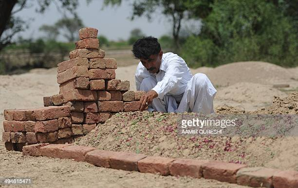 Pakistani resident Mohammad Iqbal sits beside the grave of his wife Farzana Parveen who was beaten to death with bricks by her father and other...