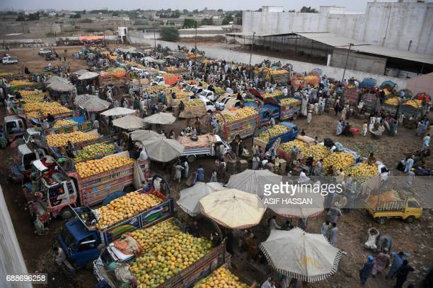 Pakistani residents buy fruits at a market in Karachi on May 26 2017 Pakistan's economy expanded almost 53 percent in the last year the country's...