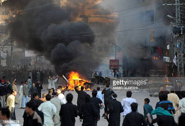 Pakistani residents gather near burning shops at a market following clashes during an Ashura procession in Rawalpindi on November 15 2013 Sectarian...