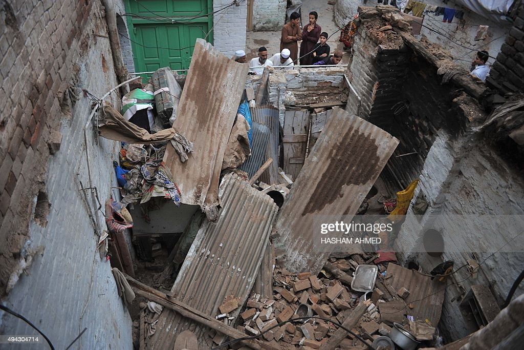 Pakistani residents look at a damaged house following an earthquake in Peshawar on October 26 2015 A powerful 75 magnitude earthquake killed at least...