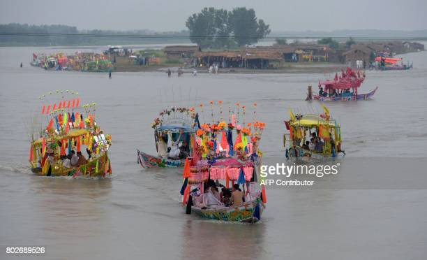Pakistani residents ride on boats in the Kabul River near Charsadda district in the Khyber Pakhtunkhwa province on June 28 on the third and last day...
