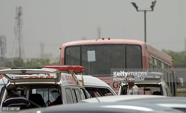 Pakistani residents stand beside a bus that was carrying Shiite Muslim parked at a hospital following an attack by gunmen in Karachi on May 13 2015...