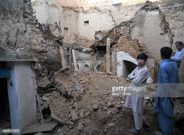 Pakistani residents stand on the rubble of houses after an earthquake in Kohat on October 26 2015 A powerful 75 magnitude earthquake killed at least...