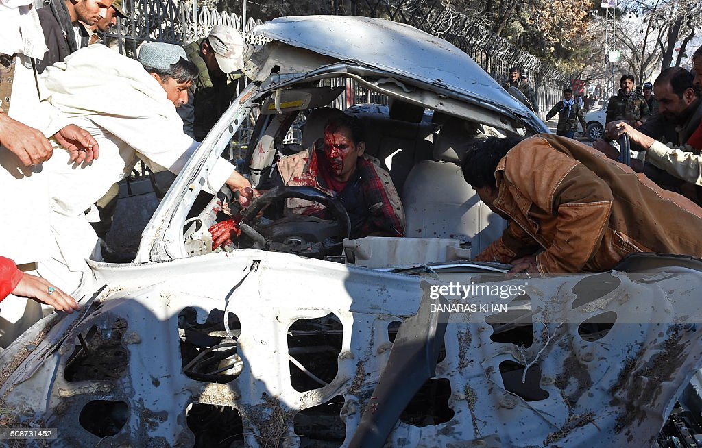 Pakistani residents try help an injured man trapped in a damaged car at the site of a bomb explosion that targeted a security convoy in Quetta on February 6, 2016. A bomb blast struck a paramilitary vehicle and killed at least eight people and wounded more than 35 others in southwestern Pakistani city of Quetta, official said. AFP PHOTO / BANARAS KHAN / AFP / BANARAS KHAN