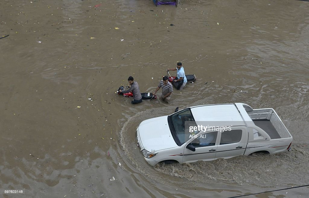 Pakistani residents wade through floodwaters following heavy rain in Lahore on August 29 2016 / AFP / ARIF ALI