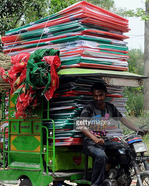 A Pakistani rickshaw driver prepares to deliver flags and posters of the political party Pakistan Tehreek Insaf in Lahore on April 13 for the...