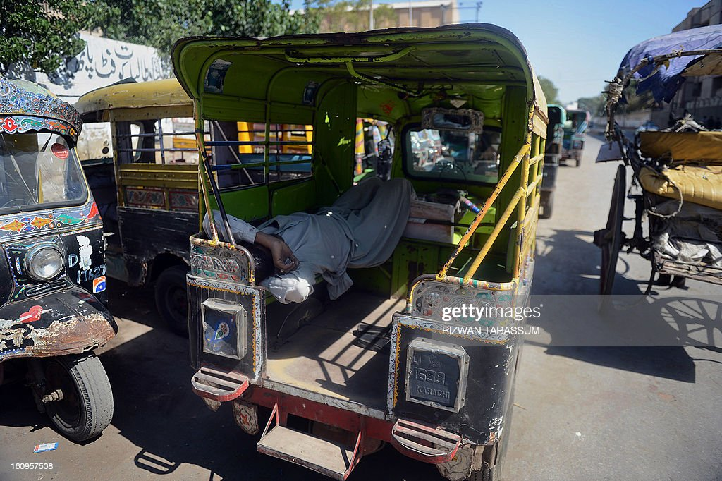 A Pakistani rickshaw driver sleeps at a bus stop during a strike in Karachi on February 8, 2013. Schools and businesses went on strike in Pakistan's financial capital Karachi on Friday as the country's top court accused the government of failing to prevent record levels of unrest. AFP PHOTO/Rizwan TABASSUM