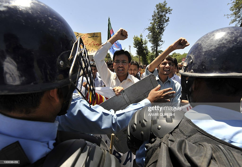 Pakistani riot police cordon off a street as Pakistani activists of Islami Jamiat-e-Tulaba (IJT), a student wing of hardline party Jamaat-i-Islami (JI), shout slogans during a protest in Islamabad on May 20, 2010, against the published caricatures of Prophet Mohammed on Facebook. Pakistan blocked access to the popular video website YouTube in a bid to contain 'growing sacrilegious' material one day after banning Facebook for a similar reason, officials said.