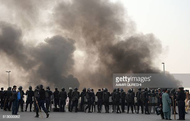 TOPSHOT Pakistani riot policemen watch as supporters of former police bodyguard Mumtaz Qadri burn tires during a protest against Qadri's execution in...