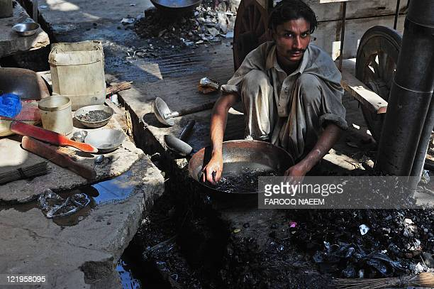 A Pakistani scavenger looks for gold in drainage's at the gold market in Rawalpindi on August 19 2011 The price of gold hit a record high above $1863...