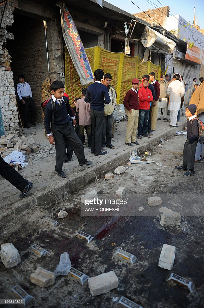 Pakistani school children gather at the site of an overnight suicide bomb attack on minority Shiite Muslims procession in Rawalpindi on November 22, 2012. A suicide bomber struck a night-time Shiite march in Pakistan, in the bloodiest attack of a day of violence that left at least 28 people dead as Islamic leaders gathered for a rare summit in Islamabad. Police in the garrison city of Rawalpindi near the capital said the attack on the procession of minority Shiite Muslims killed at least 16 people, after the suicide bomber blew himself up when he was stopped for a security check. AFP PHOTO/Aamir QURESHI