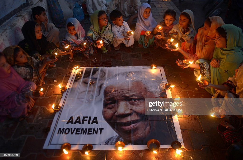 Pakistani schoolchildren hold lamps during a memorial tribute to South African late president Nelson Mandela, in Karachi on December 6, 2013. People gathered in cities around the world to make their own personal tributes to Nelson Mandela on December 6, leaving flowers and setting up makeshift shrines in an outpouring of emotion for South Africa's anti-apartheid icon. AFP PHOTO/RIZWAN TABASSUM