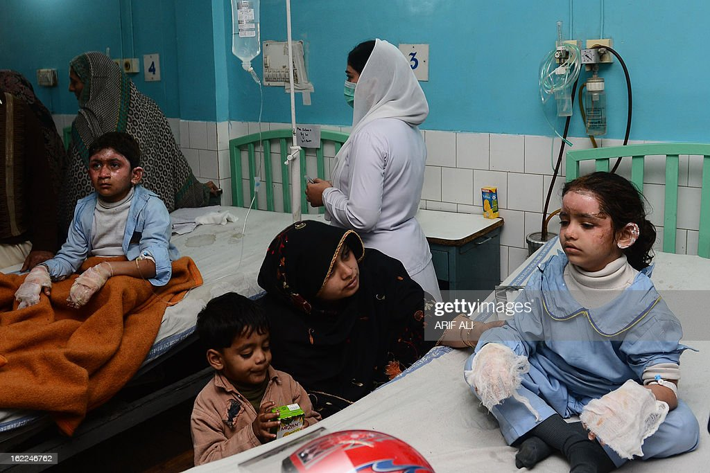 Pakistani schoolchildren (L and R) recuperate at a hospital ward in Lahore on February 21, 2013. Over 21 children and a teacher were treated for burn injuries when a fire broke out in a school classroom in Lahore. AFP PHOTO/Arif ALI