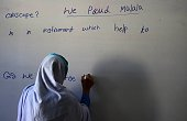 A Pakistani schoolgirl writes on a blackboard during class after offering prayers for Nobel Peace Prize laureate Malala Yousafzai during a school...