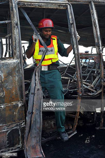 A Pakistani search and rescue team member exits the wreckage of a burnt bus after the compressed natural gas cylinders powering it exploded while it...