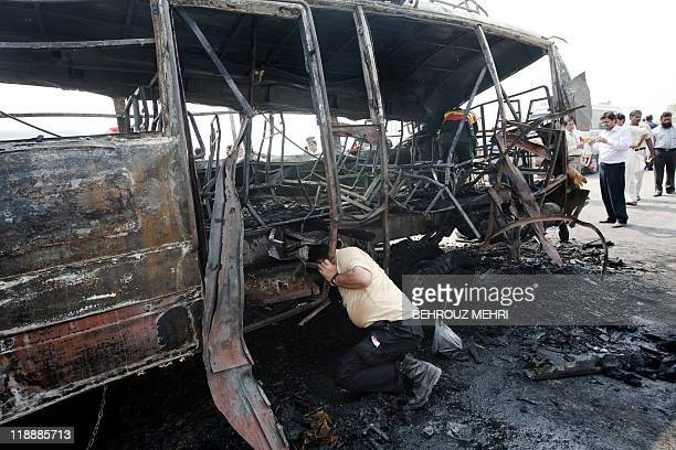 A Pakistani search and rescue team member inspects a burnt bus after the compressed natural gas cylinders powering it exploded while it was on a...