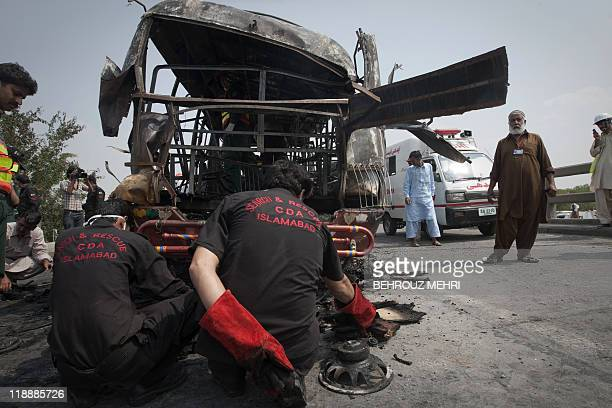 Pakistani search and rescue team members inspect a burnt bus after the compressed natural gas cylinders powering it exploded while it was on a...