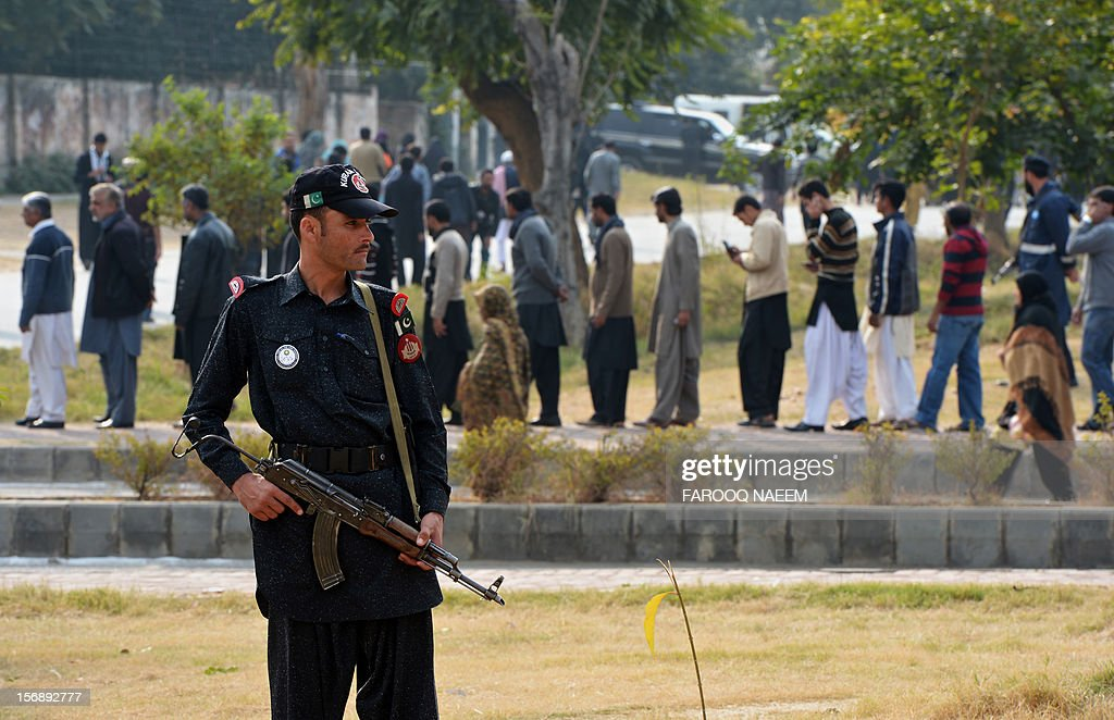 A Pakistani security officer stands guard as Shiite Muslims lineup for a security check during a religious procession on the ninth day of holy month of Moharram in Islamabad on November 24, 2012. The Pakistani Taliban have claimed responsibility for a bomb blast near a Shiite Muslim procession in northwest Pakistan that killed seven people. The blast went off as people from the minority Shiite Muslim community were gathering to mark the anniversary of the death of the Prophet Mohammed's grandson Imam Hussain in 680. AFP PHOTO/Farooq NAEEM