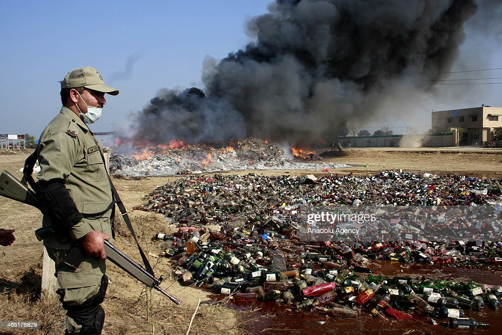 A Pakistani security official stands guard as customs officials use a steamroller to crush bottles of liquor at a ceremony on the International Customs Day in the outskirts of Lahore, on January 26, 2014.