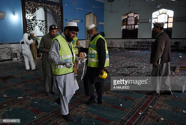 Pakistani security officials and volunteers collect evidence at a Shiite Muslim mosque after it was attacked by Taliban militants in Peshawar on...