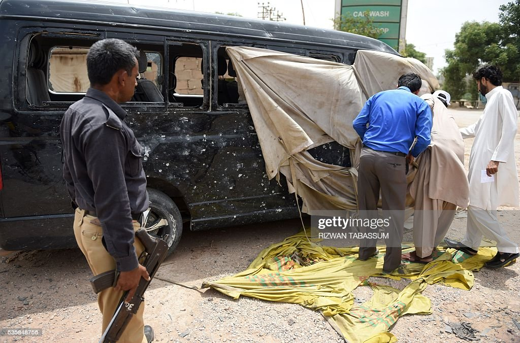 Pakistani security officials examine a damaged vehicle in which a Chinese National was travelling, following a roadside bomb attack in Karachi on May 30, 2016. A Chinese worker and his Pakistani driver were wounded in the bomb attacked in Karachi on May 30, which has been claimed by ethnic nationalists opposed to plans for extensive Chinese investment, police said. / AFP / RIZWAN