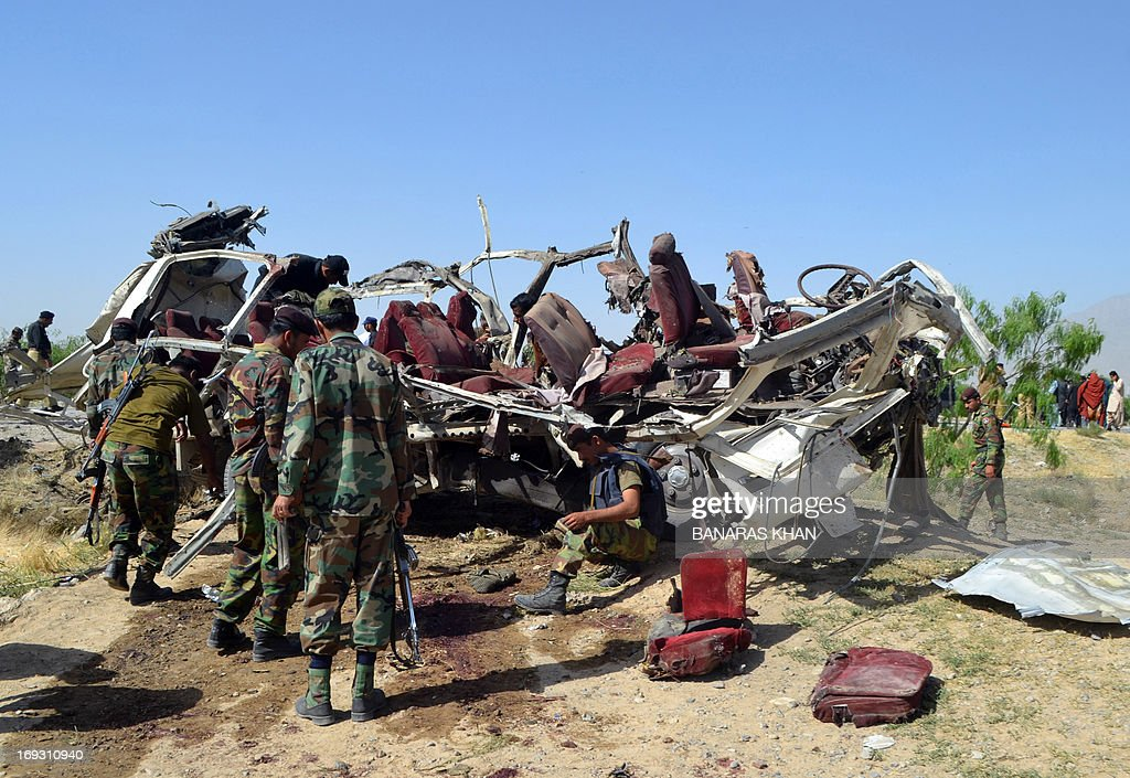 Pakistani security officials examine the destroyed vehicle used by security forces following a bomb attack on the outskirts of Quetta, the capital of restive Baluchistan province, on May 23, 2013. A bomb planted in a rickshaw tore through a vehicle used by security forces in southwest Pakistan on May 23, killing at least 12 people, police said. AFP PHOTO / BANARAS KHAN