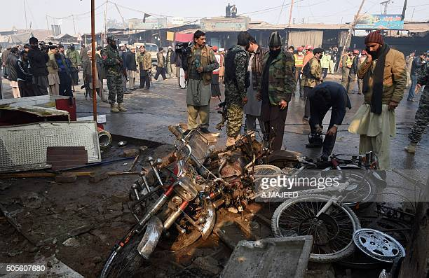Pakistani security officials examine the site of a suicide bomb attack on the outskirts of Peshawar on January 19 2016 At least nine people were...