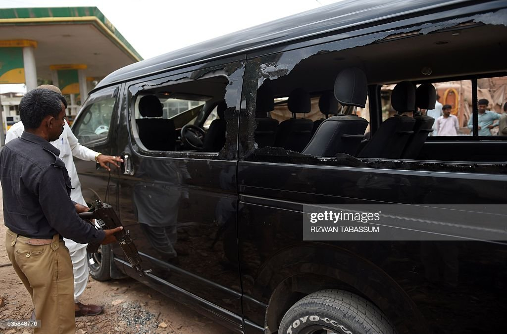 Pakistani security officials inspect a damaged vehicle in which a Chinese National was travelling, following a roadside bomb attack in Karachi on May 30, 2016. A Chinese worker and his Pakistani driver were wounded in the bomb attacked in Karachi on May 30, which has been claimed by ethnic nationalists opposed to plans for extensive Chinese investment, police said. / AFP / RIZWAN