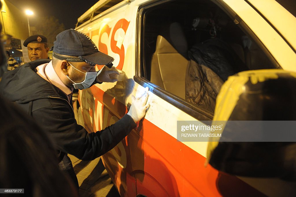 Pakistani security officials inspect a DSNG (digital satellite news gathering) vehicle of a private news channel following an attack by gunmen in Karachi late on January 17, 2014. Gunmen shot dead a senior sunni religious leader and two of his associates in the southern Pakistani city of Karachi on January 17, police said, while a separate attack killed three people who worked for a private television channel. AFP PHOTO/Rizwan TABASSUM