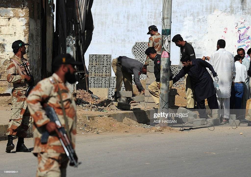 Pakistani security officials inspect the site of a bomb explosion in Karachi on Novmeber 26, 2012. A bomb attack killed a labourer and wounded four passers-by, officials said. The blast was detonated by a mobile phone and authorities said they believed it had been planted to target a procession of Shiite Muslims who had been scheduled to pass through the area in recent days. AFP PHOTO/Asif HASSAN