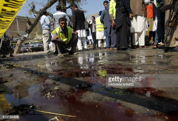 TOPSHOT Pakistani security officials inspect the site of a suicide bombing in Shabqadar on March 7 2016 A suicide bomber killed 13 people and injured...