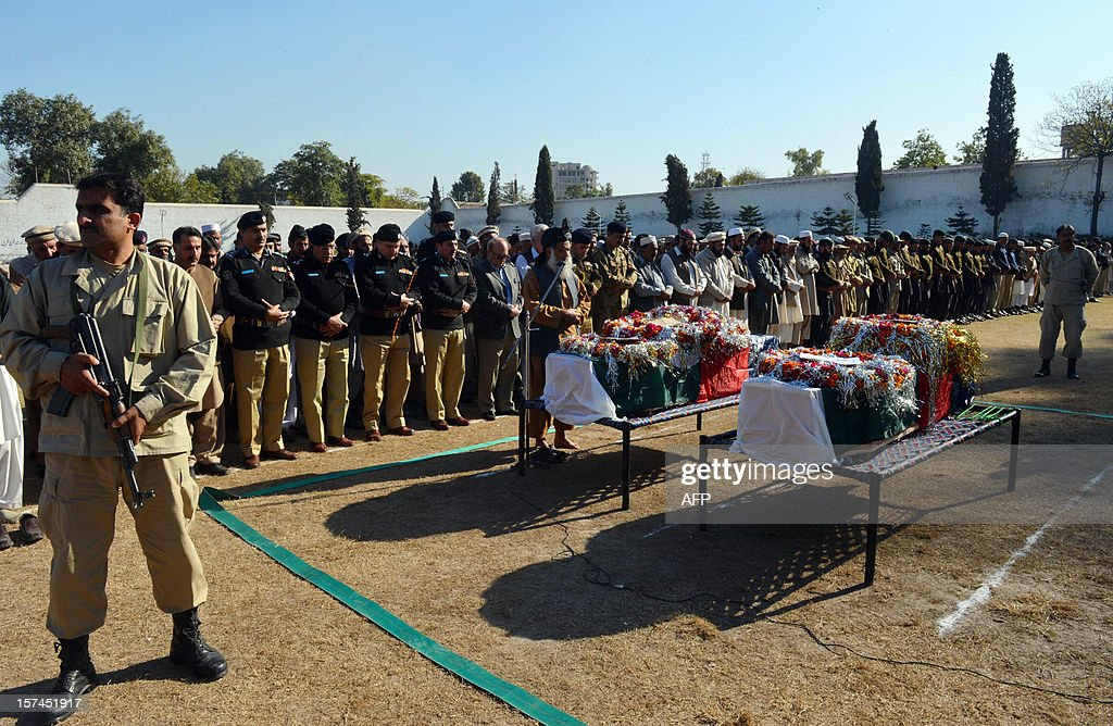 Pakistani security officials offer funeral prayers for their police officers who were killed in a bomb explosion in Peshawar on December 3, 2012. Bombers attacked a Pakistani police patrol on December 3, killing two officers and wounding two others on the outskirts of the main northwestern city of Peshawar, police said.