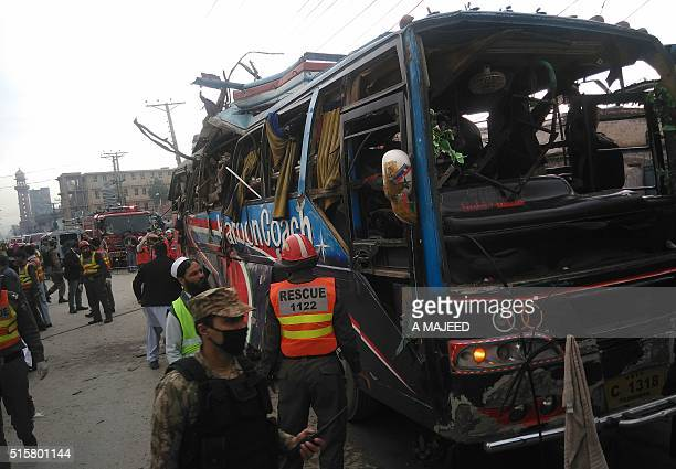 Pakistani security officials search a damaged bus after a bomb blast in Peshawar on March 16 2016 A blast ripped through a bus carrying government...