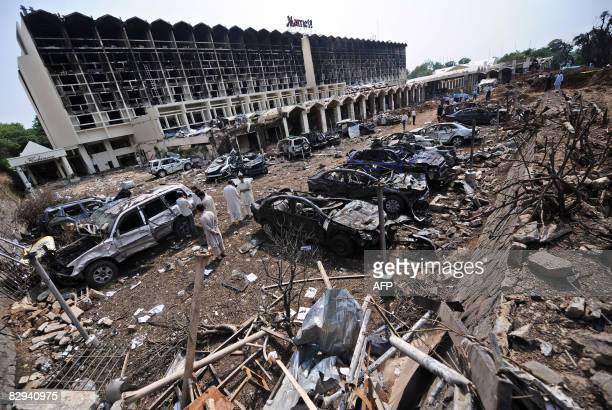 Pakistani security personell investigate the destroyed vehicles at the parking area of the devastated Marriott Hotel in Islamabad on September 21...