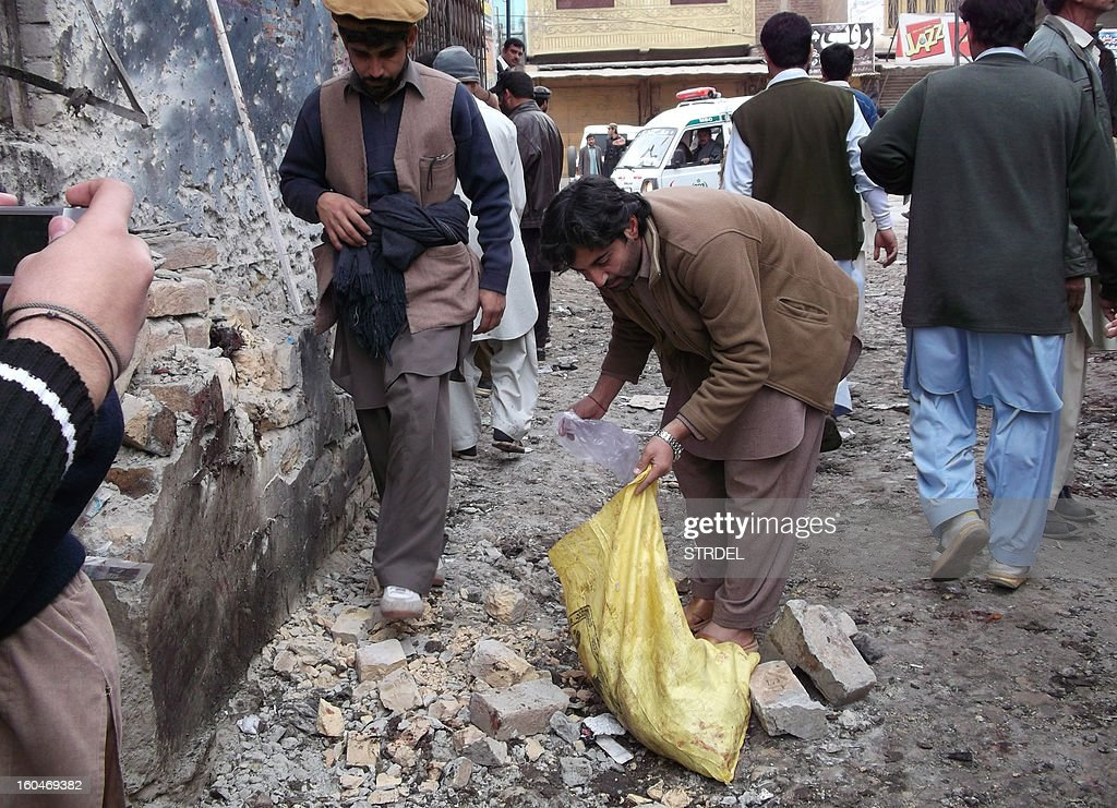 Pakistani security personnel collect evidence at the site of a bomb blast outside a Shiite Muslim mosque in Hangu on February 1, 2013. A suicide bomber targeted a Shiite Muslim mosque in northwest Pakistan on Friday, killing 21 people and wounding up to 50 as worshippers poured out of weekly prayers, officials said.