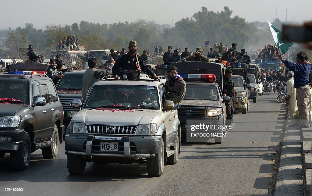 Pakistani security personnel escort the convey of Pakistani religious leader Tahir-ul Qadri at a protest march in Sohawa, some 80 kms from Islamabad on January 14, 2013. Tens of thousands of Pakistani protesters streamed towards Islamabad on Monday, led by a cleric calling for revolution but accused of trying to sow political chaos ahead of elections. AFP PHOTO/Farooq NAEEM