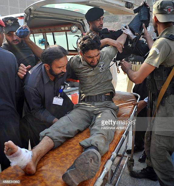 Pakistani security personnel help an injured comrade to a hospital following an attack by militants on a Pakistan Air Force base in Peshawar on...