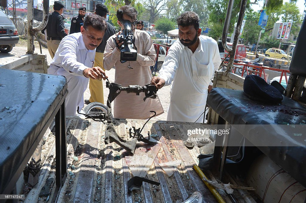 Pakistani security personnel hold up a mangled section of a motorcycle to a media representative at the bomb blast site in Peshawar on April 29, 2013. A suicide bomber killed at least eight people and wounded 45 others when he rammed his motorcycle into a bus in Pakistan's northwestern city of Peshawar on Monday, police said. AFP PHOTO/A MAJEED