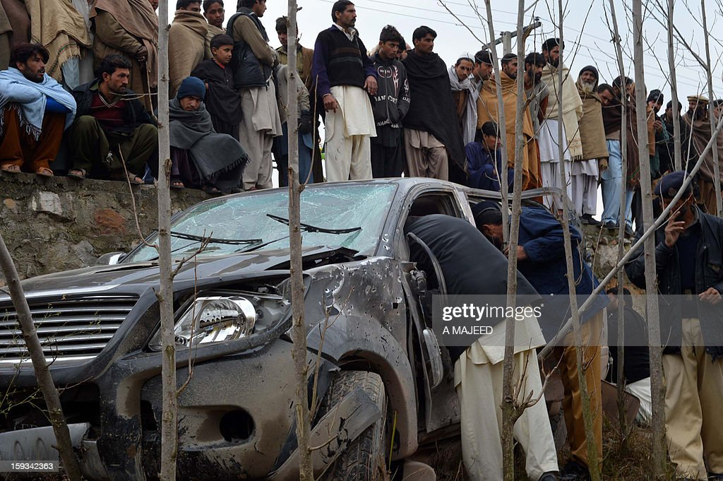 Pakistani security personnel inspect a damaged car after the local political leader's convoy was attacked in Pakistan's northwest city of Charsadda on January 12, 2013. Several people were injured in the roadside bomb blast which targeted the local political leader of the secular Awami National party Bashir Omarzai who survived the attack.