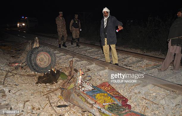Pakistani security personnel inspect wreckage of van following an overnight accident where a train collided with a minivan in Allah Dino Sand near...