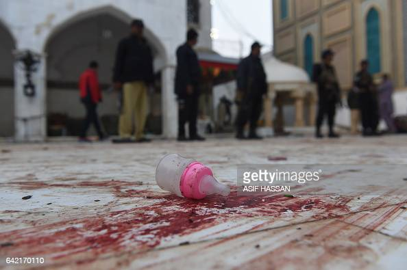 TOPSHOT Pakistani security personnel stand guard at the 13th century Muslim Sufi shrine of Lal A baby feeder lies on the bloodstained floor at the...
