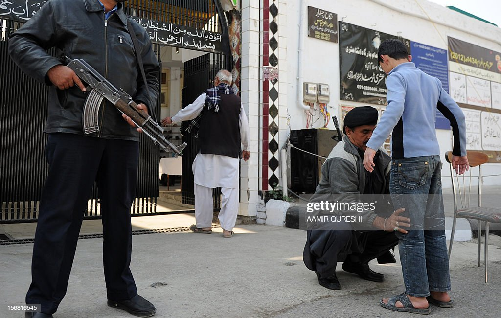 A Pakistani security serviceman frisks a worshipper before entering a Shiite Muslim mosque following overnight suicide bomb attacks on minority Shiite Muslims, in Islamabad on November 22, 2012. Muslim leaders gathered for a rare summit in Islamabad on November 22 as militant attacks killed 35 people across the country on one of the deadliest days of violence claimed by the Taliban in months. Twenty-three people were killed and 62 wounded overnight in Rawalpindi, the twin city of Islamabad, where Iranian President Mahmoud Ahmadinejad and Turkish Prime Minister Recep Tayyip Erdogan are chief among the summit guests. AFP PHOTO/Aamir QURESHI