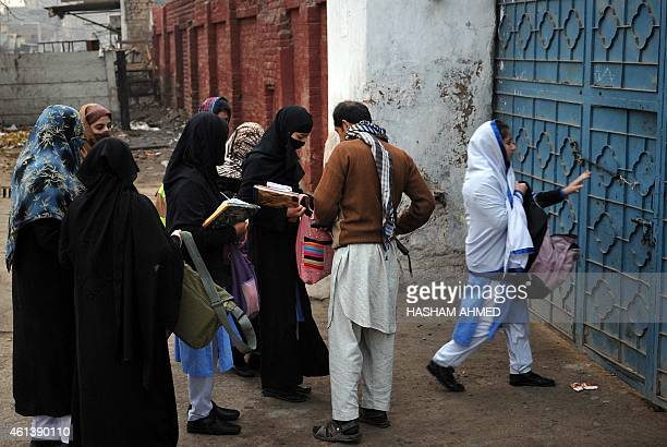 A Pakistani security staff member searches the bags of students entering a government school after schools in the city reopened following a Taliban...