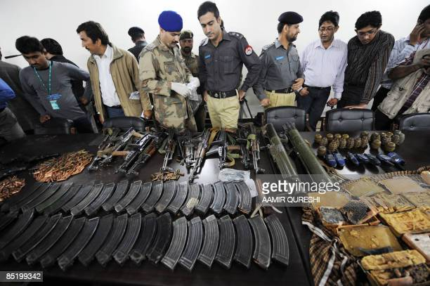 Pakistani securuty officials display the weapons used by gunmen during an attack on the Sri Lankan cricket team in Lahore on March 3 2009 Attackers...